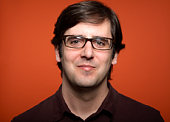Man wearing glasses, against orange background, portrait