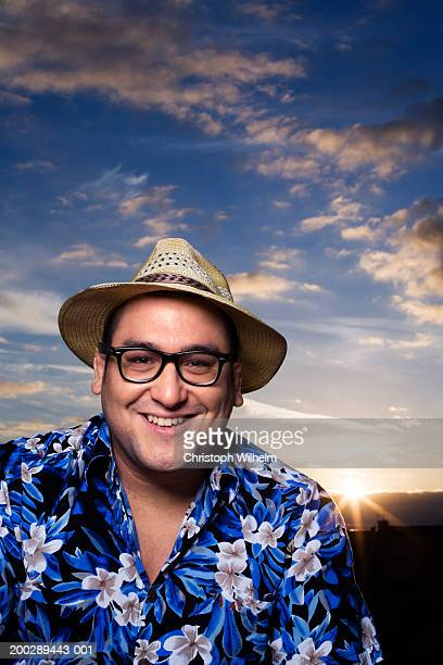 Man wearing glasses and hat, smiling, portrait, sunset