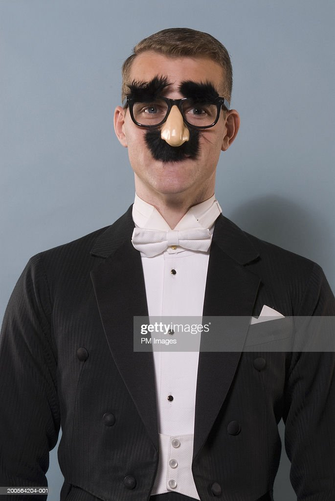 Man wearing Groucho Marx mask and comedy glasses, portrait, close-up : Stock Photo