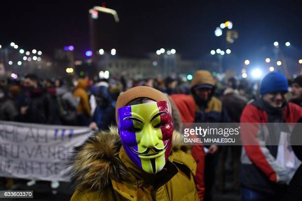 TOPSHOT A man wearing Guy Fawkes mask painted in the colors of Romanian flag looks on during a protest in front of the government headquarters...
