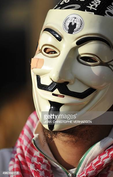 A man wearing Guy Fawkes masks demonstrates prior to the trial of three 'Anonymous' for their alleged involvement in cyber attacks targetting...
