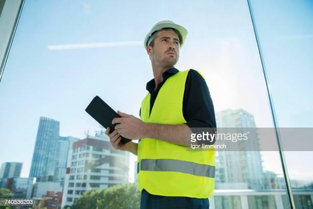 Man wearing hard hat and hi vis vest, holding digital tablet
