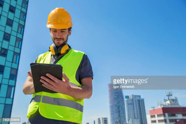Man wearing hard hat and hi vis vest, outdoors, using digital tablet