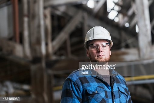 Man wearing hardhat, safety goggles and plaid shirt