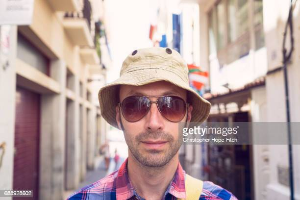 Man wearing hat and sunglasses in a Spanish street