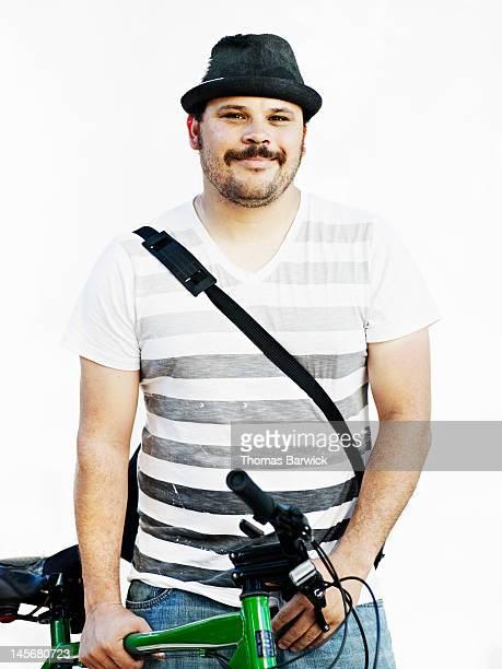Man wearing hat holding bicycle smiling