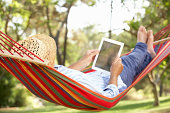 Senior Man Relaxing In Hammock With E-Book Lying Down Wearing Straw Hat
