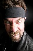 Man wearing headband, with broken teeth, grimacing, close-up, portrait