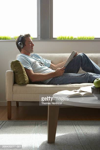 Man wearing headphones and reading newspaper on sofa, side view