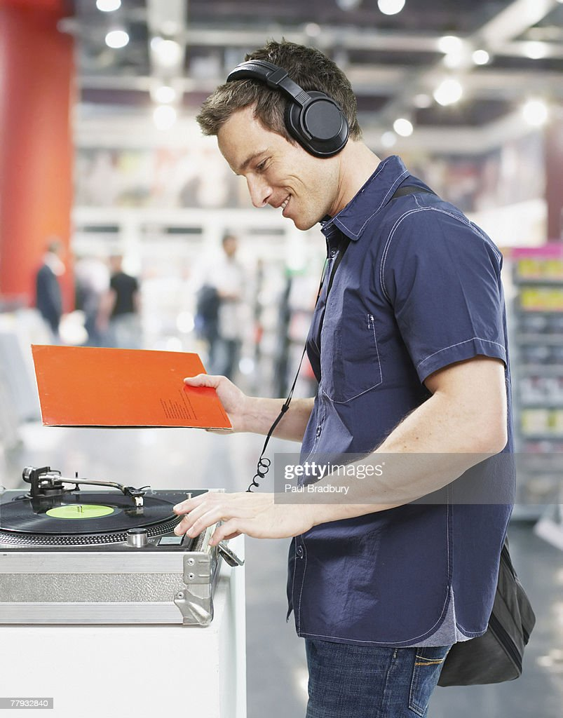 Man wearing headphones at record player in store : Stock Photo