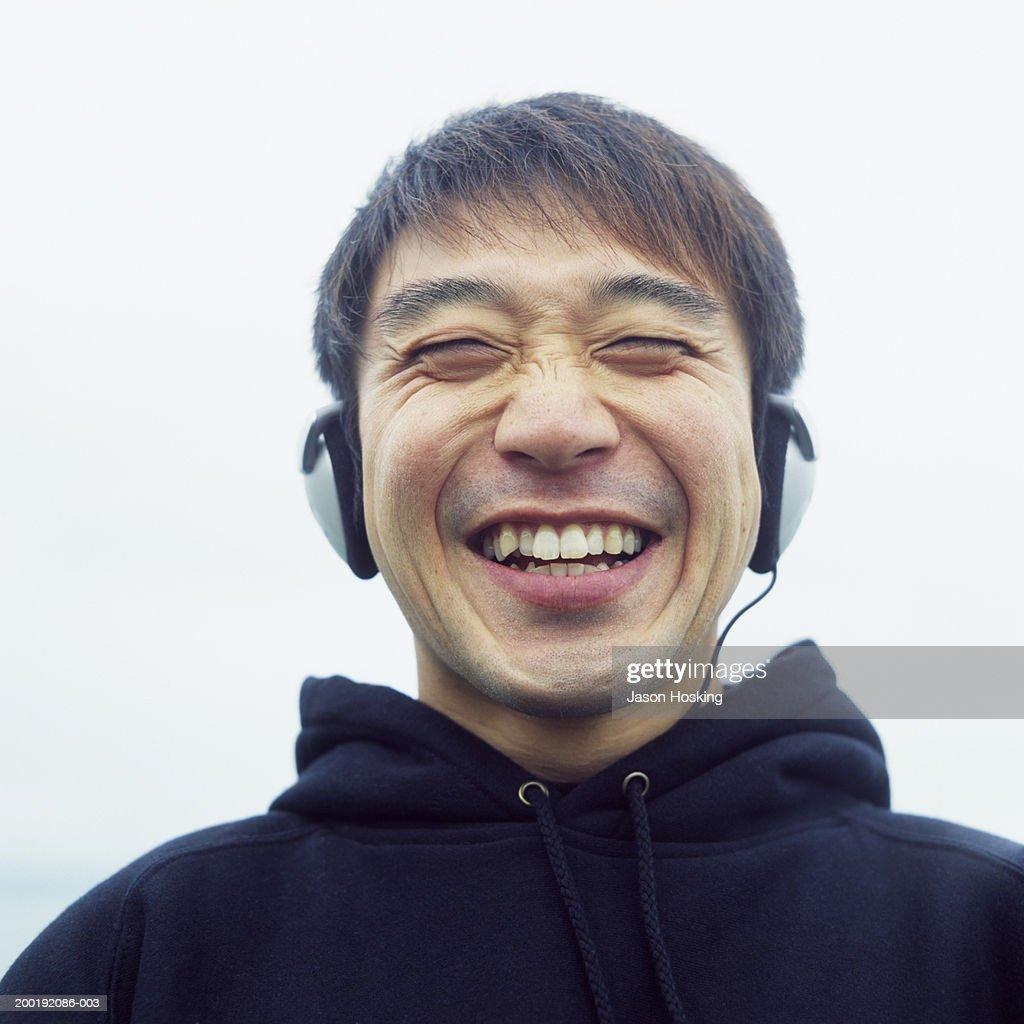 Man wearing headphones, laughing : Stock Photo