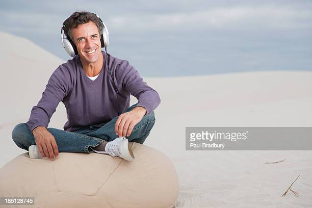 A man wearing headphones on a beanbag chair outdoors