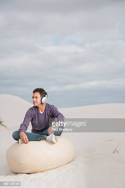 A man wearing headphones on a beanbag chair outdoors