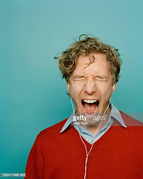 Man wearing headphones with eyes closed and shouting