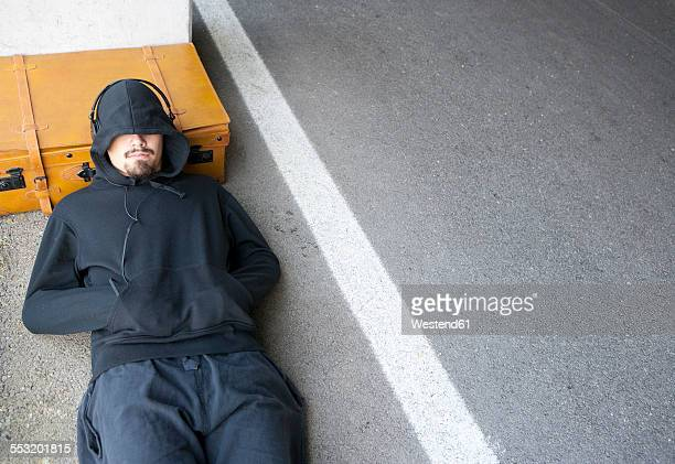 Man wearing hooded jacket sleeping beside lane