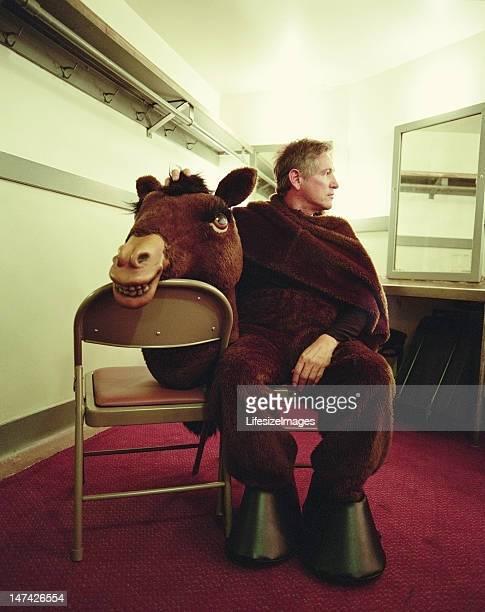 Homme portant costume de cheval, assis dans les vestiaires
