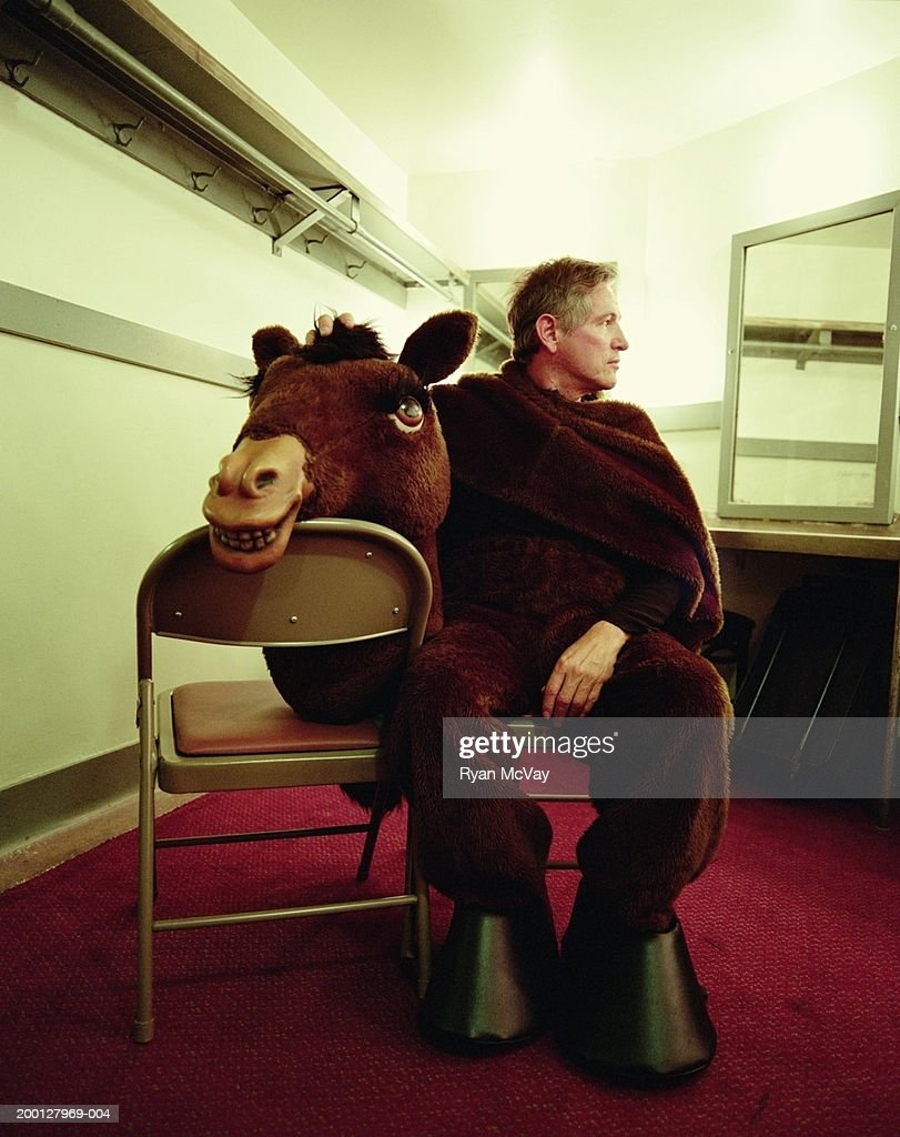Man wearing horse costume, sitting in dressing room : Stock Photo