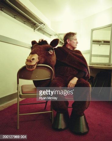 Man wearing horse costume, sitting in dressing room : Foto de stock