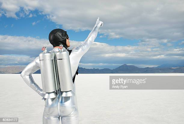 Man Wearing Jet Pack Pointing to Sky.