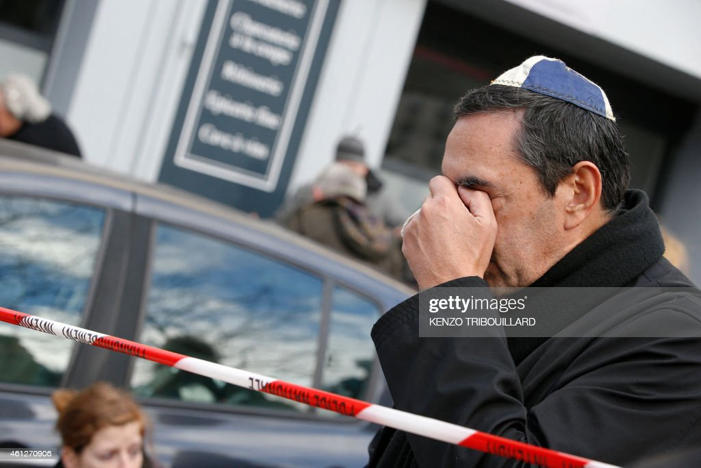 A man wearing kippa cries near a kosher grocery store in Porte de Vincennes eastern Paris on January 10 2015 a day after four people were killed at...