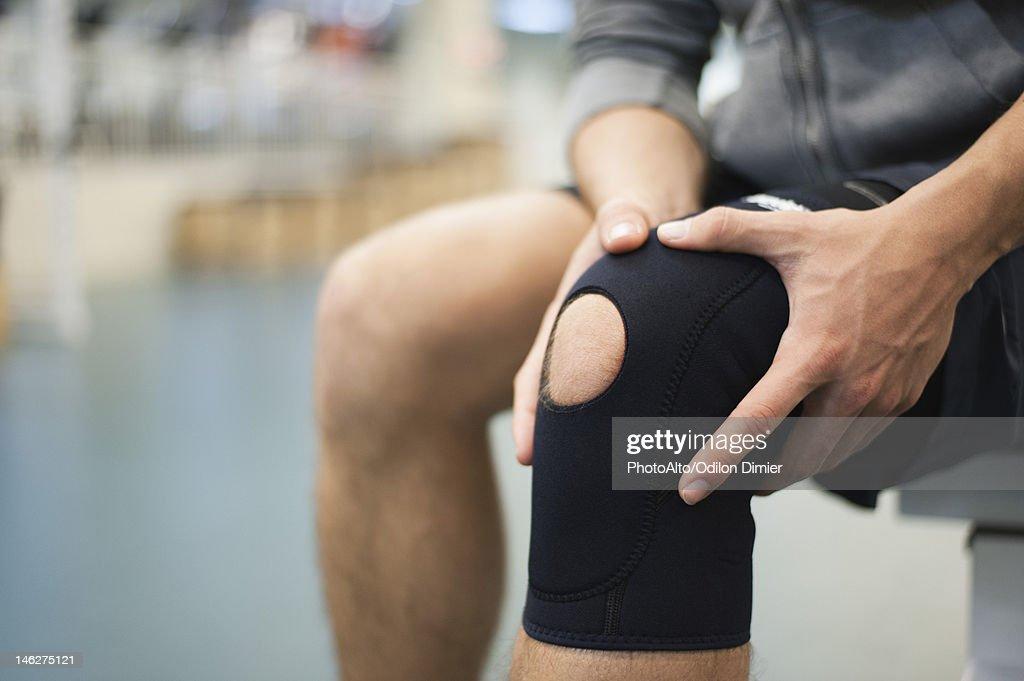 Man wearing knee brace, cropped