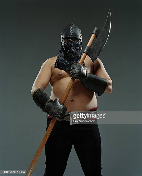 Man wearing leather helmet and mask holding ax