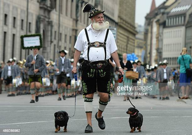 A man wearing leatherhose the traditional Bavarian clothes walks with two dogs during the traditional costume parade at the Oktoberfest beer festival...