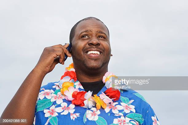 Man wearing leis using mobile phone, smiling, low angle view, close-up