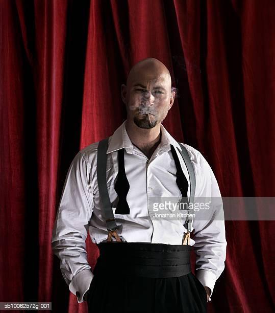 Man wearing loosened black tie, smoking cigar, portrait