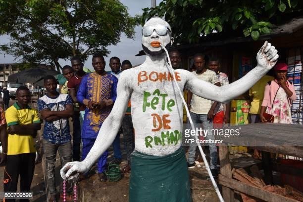 TOPSHOT A man wearing makeup reading 'Happy Ramadan' parades through the streets of Abidjan on June 25 as Muslims celebrate the Eid alFitr holiday...