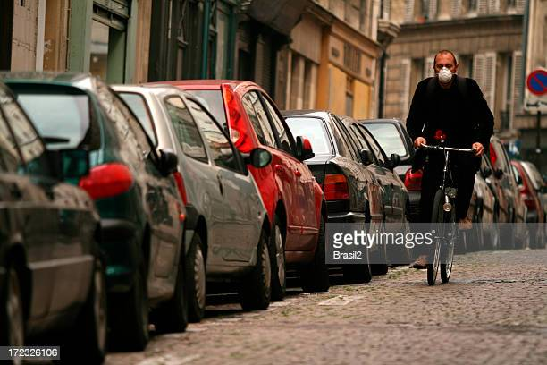 Man wearing mask biking down car lined cobblestone road