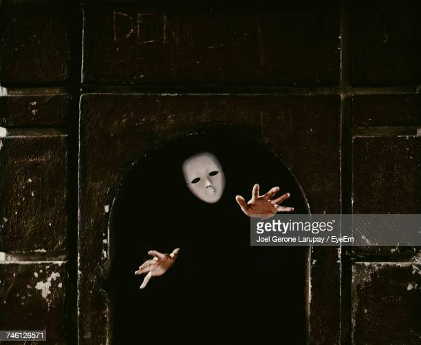 Man Wearing Mask While Gesturing In Archway