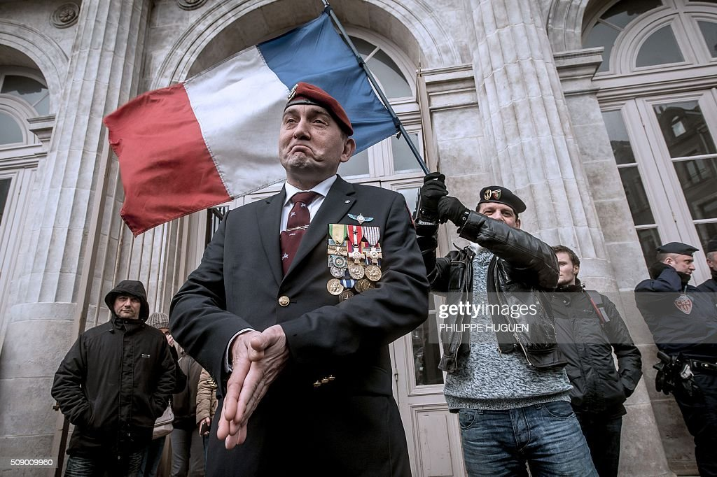 A man wearing military medals and a French Paratroopers red berret stands near a man waving a French flag on February 8, 2016 during a rally at the courthouse of Boulogne-sur-Mer, northern France in support of French General Christian Piquemal accused of taking part in a banned anti-migrants demonstration. French General Christian Piquemal is accused with four other of taking part on February 6 in a banned anti-migrants rally called by Pegida (Patriotic Europeans Against the Islamisation of the Occident) movement. His trialhas been reported for healt reasons to May 12, 2016. / AFP / PHILIPPE HUGUEN