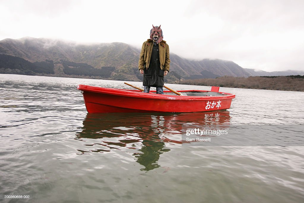 Man wearing monster mask, standing in boat : Stock Photo