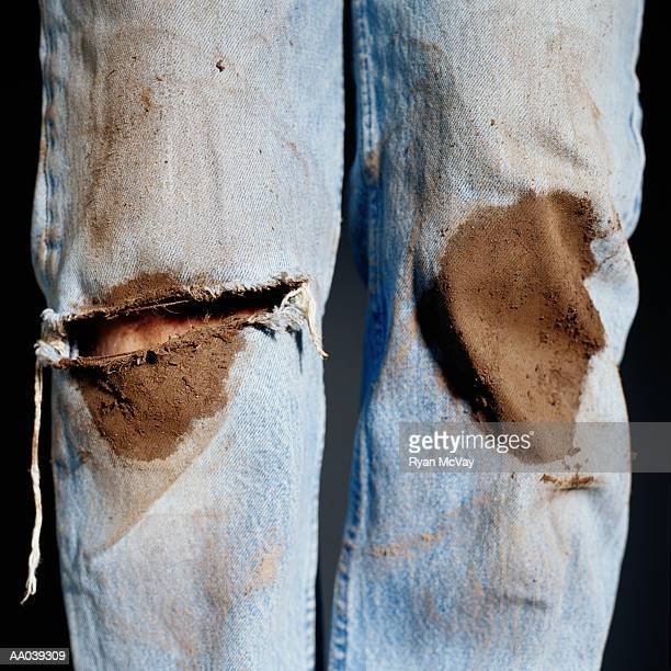 Man wearing muddy ripped jeans, close-up of knees