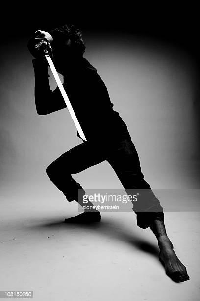 Mann trägt Ninja Kleidung und Schwert verstecken im Schatten Posieren