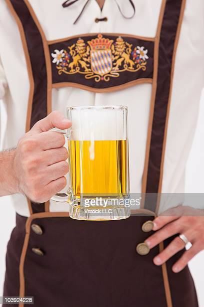Man wearing Oktoberfest costume holding a mug of beer