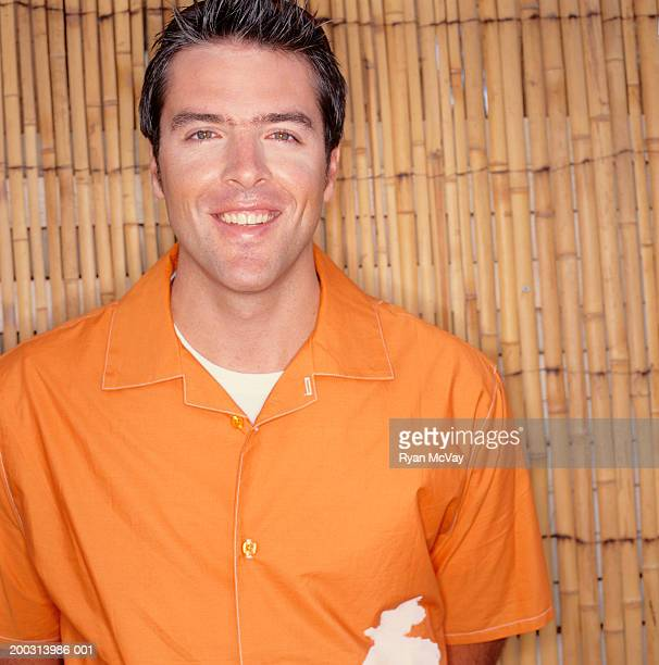 Man wearing orange shirt, standing by bamboo wall, portrait