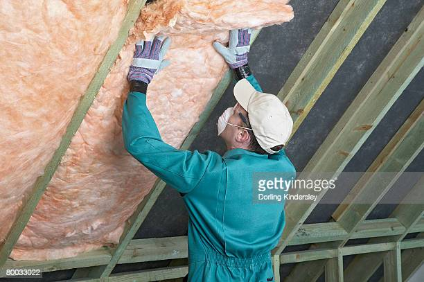 Man wearing overalls, mask, gloves and cap, filling the space between rafters with an insulation blanket