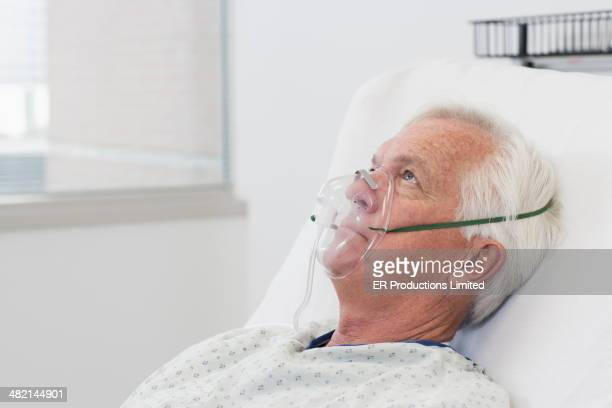 Man wearing oxygen mask in hospital bed