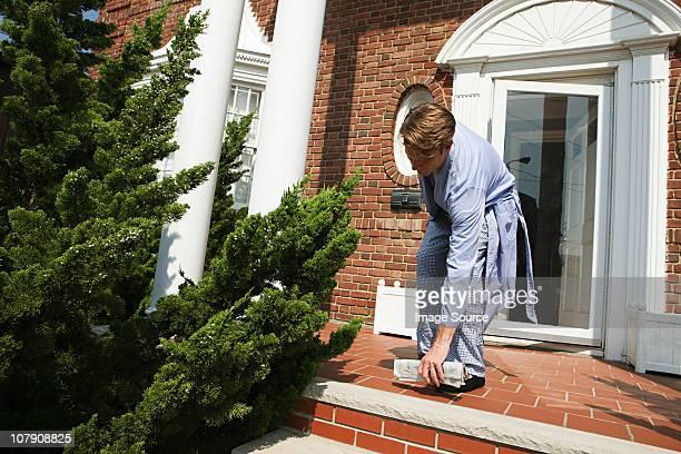 Man wearing pajamas with morning newspaper