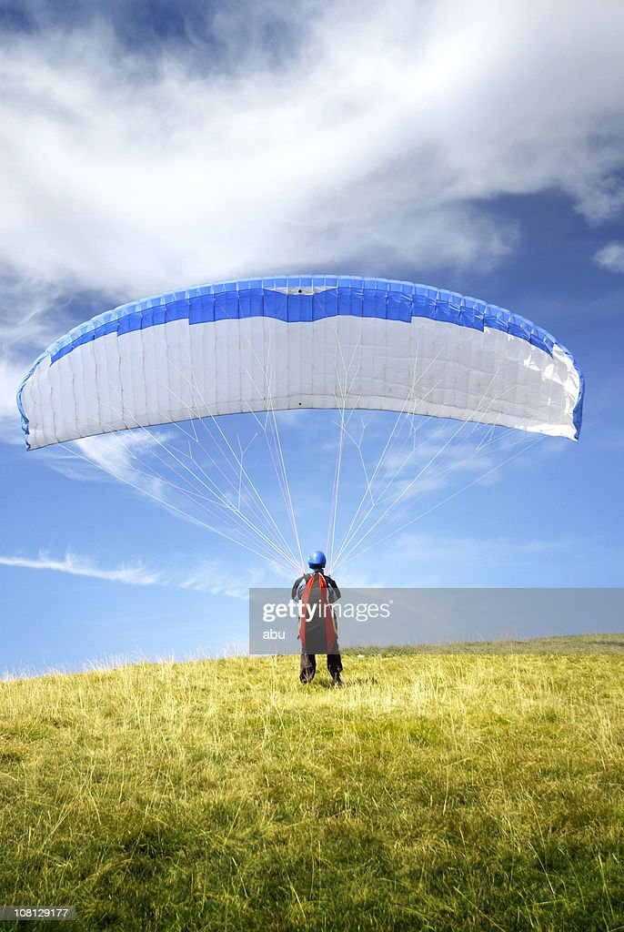 Man Wearing Parachute and Standing on Hill : Stock Photo