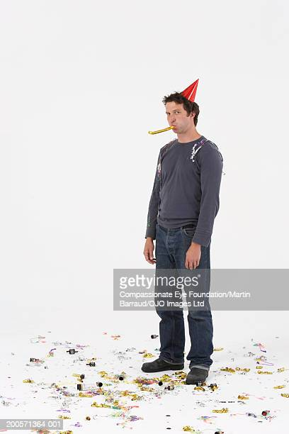 Man wearing party hat, blowing party blower, portrait