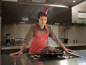 Man wearing party hat looking at burnt turkey in kitchen