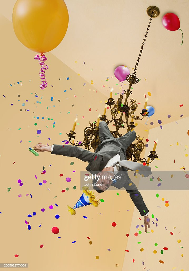 Man Wearing Party Hat Swinging From Chandelier Stock Photo