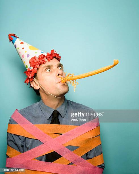 Man wearing party hat tied up in ribbons, blowing party blower