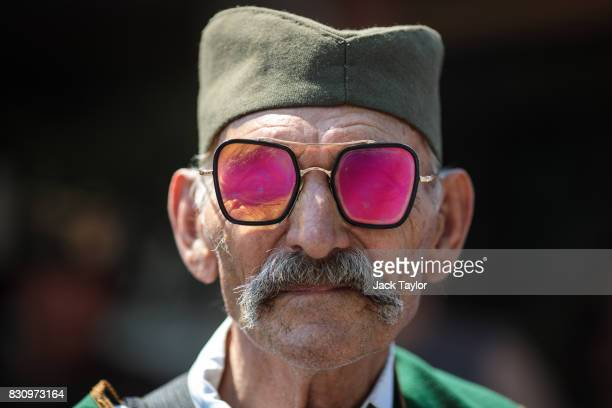 A man wearing pink tinted glasses looks on during a parade in the town centre during the Guca Trumpet Festival on August 12 2017 in Guca Serbia...