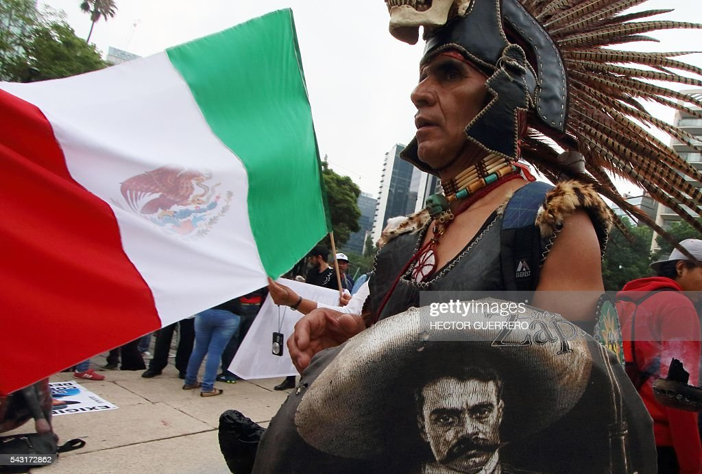 A man wearing pre-Hispanic indigenous costumes participates in a demo in support of the National Coordination of Education Workers (CNTE) teachers' union, and against an education reform launched by the government along Reforma Avenue in Mexico City on June 26, 2016. / AFP / HECTOR