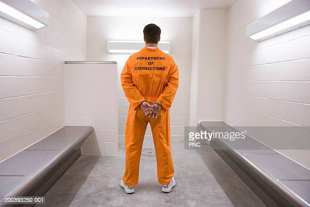 Man wearing prisoner uniform, standing in holding cell, rear view