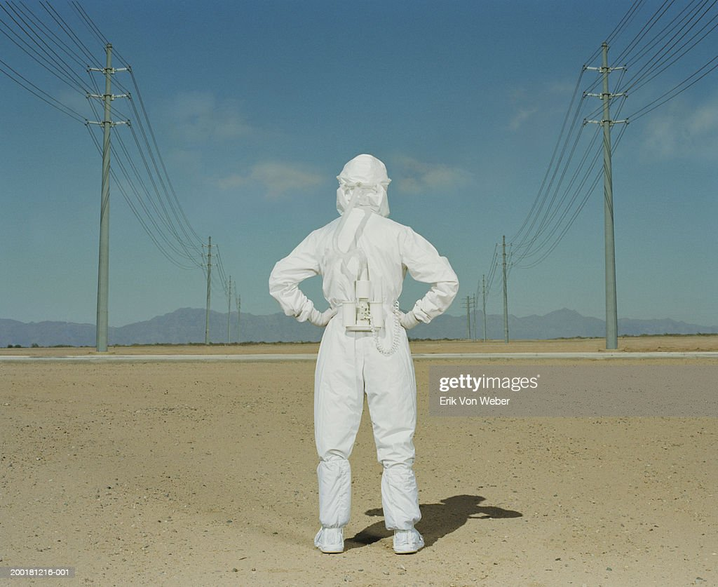 Man wearing protective suit in desert, rear view : Stock Photo